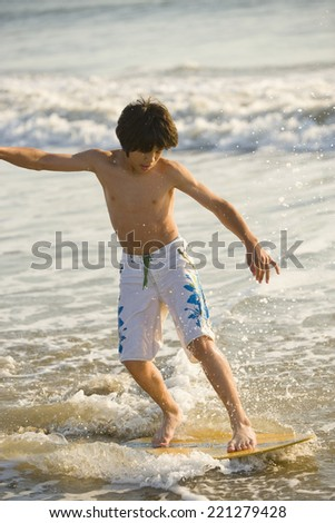 Asian boy wakeboarding - stock photo