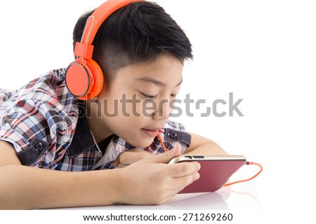 Asian boy ware headphone and playing the cell phone on whith background - stock photo