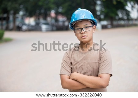 Asian boy wearing glasses, dressed as engineers work with his hands crossed.