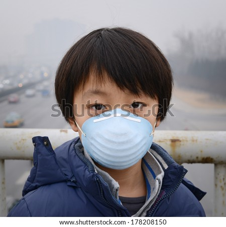 Asian boy wearing mouth mask against air pollution (Beijing) - stock photo