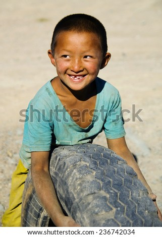 Asian boy with a beautiful smile playing with a tyre. - stock photo
