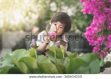 Asian boy with magnifying glass outdoors,vintage filter - stock photo