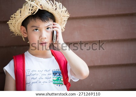 Asian boy with red backpack speaks by phone