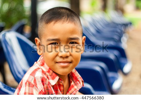 Asian boy with smiling face and waiting for his parents on blurred chair background.  - stock photo