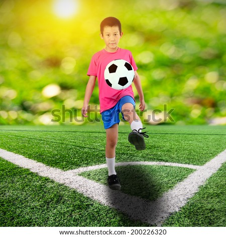 Asian boy with soccer ball on soccer field and orange bokeh and sun flare - stock photo
