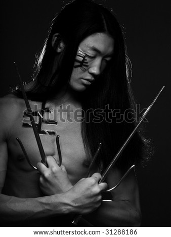 asian boy with weapons on black background
