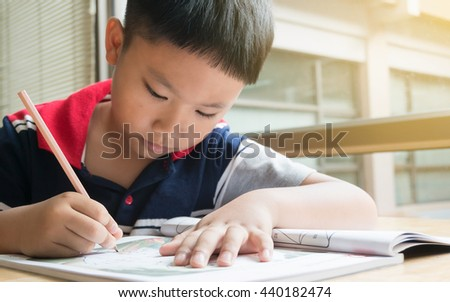 Asian Boy Writing Exercise in Library.