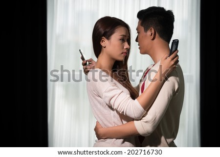 Asian boyfriend and girlfriend hugging each other but texting to other people - stock photo