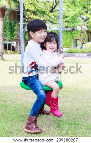 asian brother and sister playing swing at playground