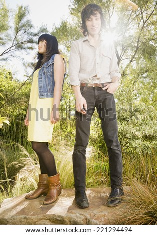 Asian brother and sister standing on rock - stock photo