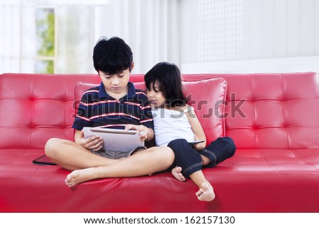 Asian brother and sister using a tablet computer on the couch - stock photo