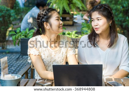 Asian businees women enjoying with her friend on laptop at coffee shop