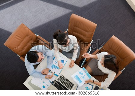 Asian business colleagues discussing financial reports, view from the top - stock photo