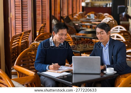 Asian business colleagues having meeting in coffee shop