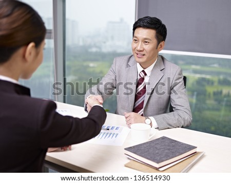 asian business executives shaking hands in office. - stock photo