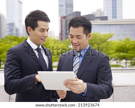 asian business executives using ipad in city park. - stock photo