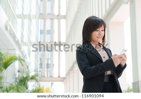 asian business girl using phone at office building - stock photo