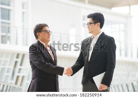 asian business handshake between senior and young business male