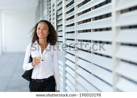 Asian business lady walking outdoors with a coffee cup - stock photo