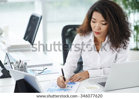 Asian business lady working with document at her workplace