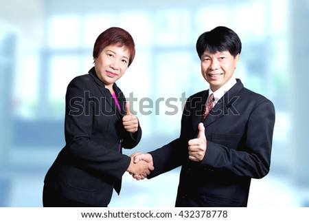 Asian business man and woman shake hand and thumb good success deal concept