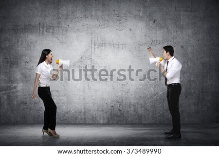 Asian business man and woman shout each other. Business competition concept - stock photo