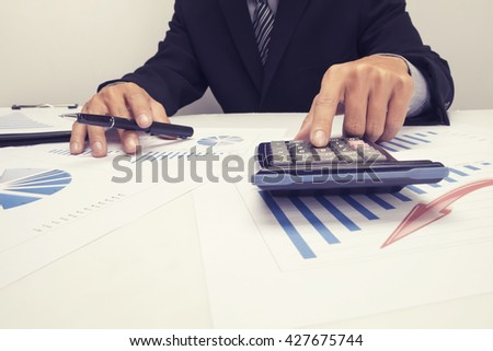 Asian Business man hand pointing at business document during discussion at meeting and  using a calculator to calculate the numbers.Vintage tone - stock photo