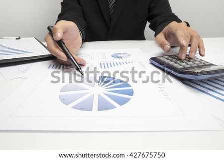 Asian Business man hand pointing at business document during discussion at meeting and  using a calculator to calculate the numbers - stock photo