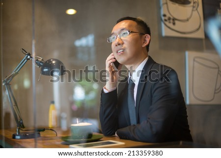 asian business man having coffee and phone conversation at cafe - stock photo