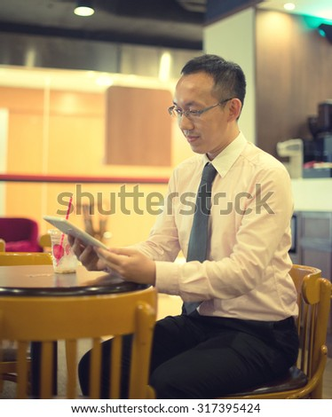 asian business man having coffee in cafe, hong kong - stock photo