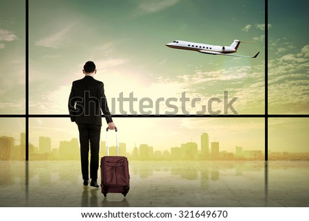 Asian business man looking the city while carry suitcase. Business travel concept