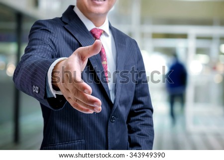 Asian business man offering handshake in office. - stock photo