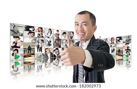 Asian business man or boss standing in front of tV screen wall showing pictures of business concept.