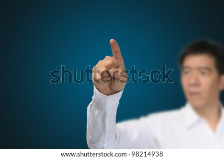 asian Business Man Pointing on gradient blue background - stock photo