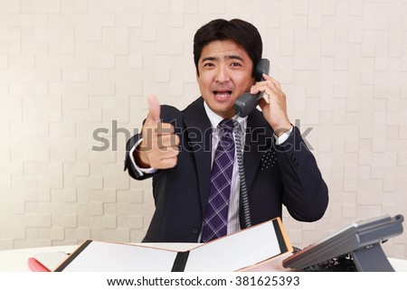 Asian business man showing thumbs up sign