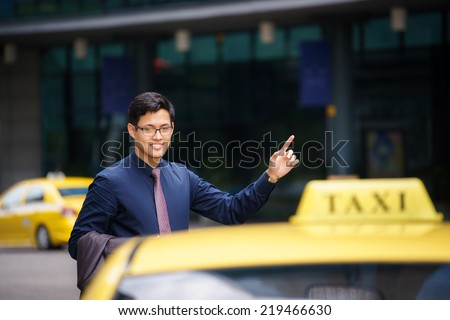 Asian business man standing near office buildings, calling yellow taxi and entering in car - stock photo