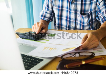 Asian Business man using a calculator to calculate the numbers - stock photo