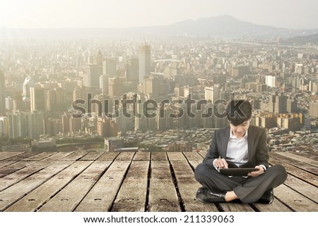 Asian business man using pad and sit on ground.