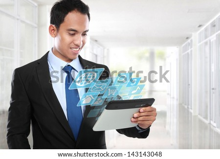 Asian Business man using tablet PC and smiling with conceptual image