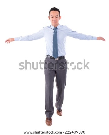 Asian business man walking balance, front view full length isolated over white background. - stock photo