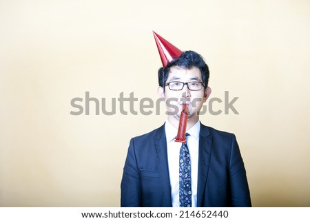 Asian business man wearing party hat - stock photo