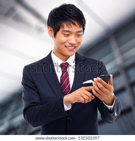 Asian business man with cellphone in business background.