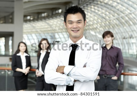 Asian Business man with colleagues in the background out of focus