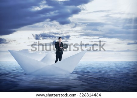 Asian business man working with laptop on the paper boat, sailing on the sea