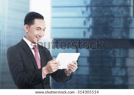 Asian business man working with tablet computer with office building background