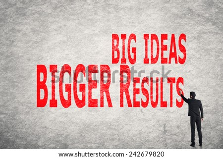 Asian business man write words on wall, Big Ideas Bigger Results - stock photo