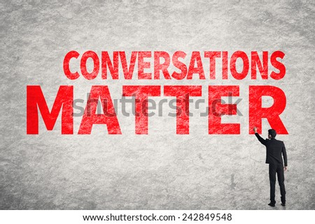 Asian business man write words on wall, Conversations Matter - stock photo