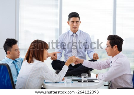 Asian business people arguing while their colleague sitting on the table in lotus position