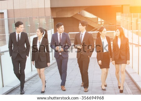 Asian business people chat and rest in the outside of office. - stock photo