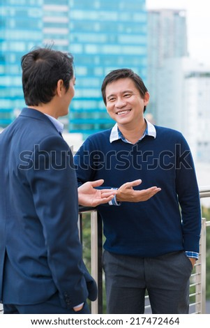 Asian business people chatting outdoors during the break - stock photo